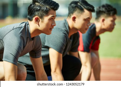 young asian track and field athletes sprinters setting on starting line.