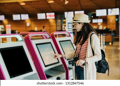Young Asian travel woman using self check-in kiosks in lobby. Technology in airport. female photographer with backpack and luggage touching monitor of auto machine to make sure her flight timetable