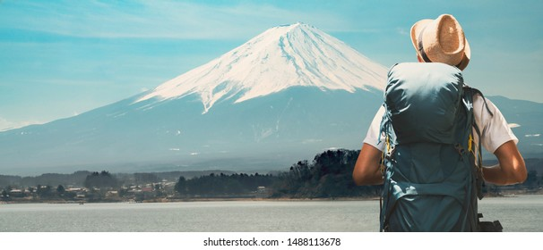 Young asian traveler with backpack in the Fuji Mountain. Hiking Fujisan volcano at Kawaguchiko lake, Japan. Backpacker standing and looking at the Mount Fuji in Japan.