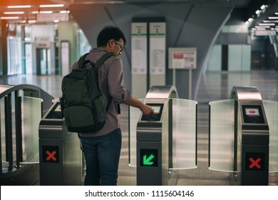 Young asian traveler using smart card pass the door at Mass Rapid Transit (MRT) train in Kuala Lumpur. MRT system forming the major component of the railway system in Kuala Lumpur, Malaysia.