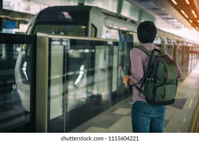 Young asian traveler waiting Mass Rapid Transit (MRT) train with background of cityscape in Kuala Lumpur. MRT system forming the major component of the railway system in Kuala Lumpur, Malaysia.