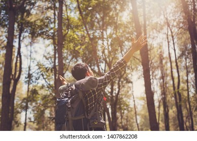 Young Asian travelers with raised hand in pine forest,Happy man deep breath fresh air in nature breathing clean air. Female enjoying nature