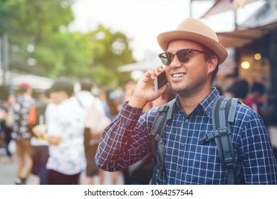 Young asian traveling man talking on phone at Chatuchak Market in Bangkok Thailand.