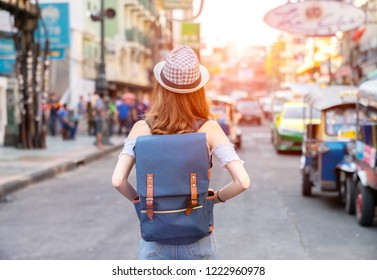 Young Asian traveling women traveling backpacker in Khaosan Road on holiday at Bangkok Thailand, traveler and tourist concept.