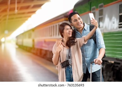 Young Asian traveller taking selfie with smartphone at train station during vacation time;Lifestyle concept.