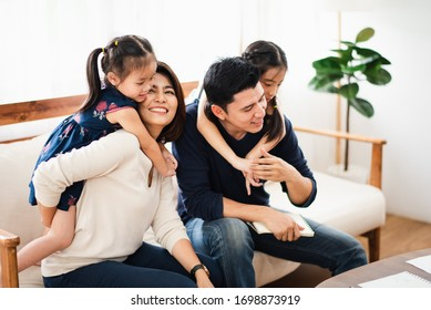 Young Asian warm love family stay in white  living room at home, parent and two daughter enjoy to playing with funny which sitting on white sofa, looking smiling and felling happy.