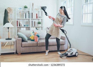 Young asian wife cleaning home playing vacuum cleaner. housewife having fun in living room while doing housekeeping in the house. happy music lady with earphones wearing apron dancing.