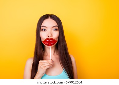 Young asian, wishing to have something lips like a lolipop she is holding, she stands in summer outfit near the copy space, on bright yellow background