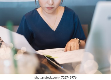 Young Asian woman administrative manager working with financial documentation and financial reports in online database checking in selective focus.