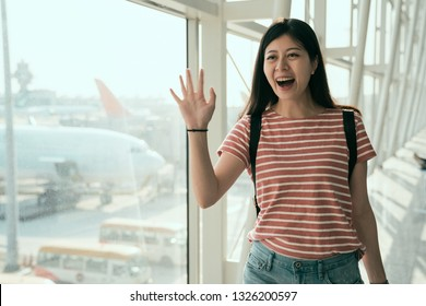 Young asian woman at the airport arrival pass customs control walking in hall. Behind the back of the passenger is airplanes on runway. happy girl waves hand saying hi to friends pick her up.