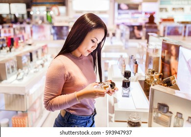 Young asian woman applying and choose to buy perfume in duty free store at international airport.