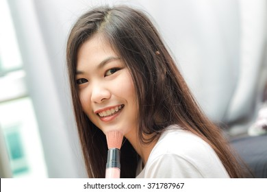 Young asian woman applying cosmetic paint brush in bedroom