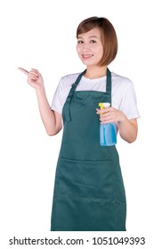 Young Asian woman in apron holding a spray and pointing isolated on white background