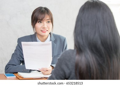Young Asian woman arriving for a job interview. Business people takling in modern office. Greeting deal concept