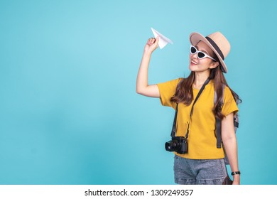 Young Asian woman backpacker traveller holding paper plane over blue background for travel concept