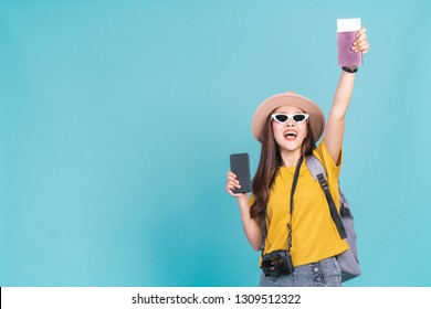 Young Asian woman backpacker traveller happy to go travel holding passport and smart phone over blue background, booking and travelling concept