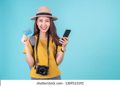 Young Asian woman backpacker traveller happy to go travel holding credit card and smart phone over blue background, booking and travelling concept