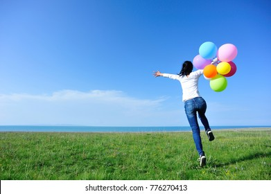 young asian woman with balloons jumping on green grassland