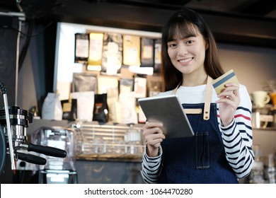 Young asian woman barista using tablet and holding credit card at cafe counter, food and drink business concept