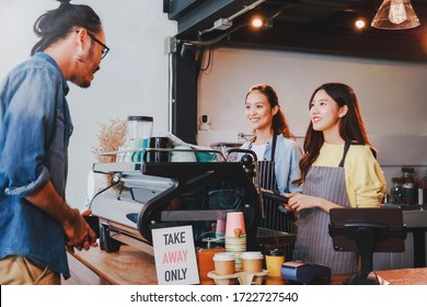 Young Asian woman barista wear apron making coffee cup served to customer at bar counter in coffee shop with smile face and takeaway orders only sign.Social distancing in situation of covid-19.