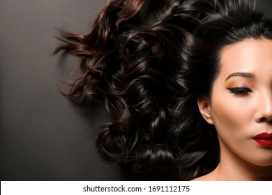 Young Asian woman with beautiful hair on dark background
