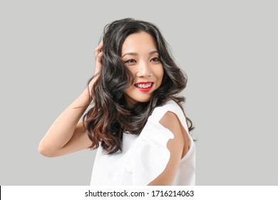 Young Asian woman with beautiful hair on grey background