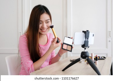 Young asian woman beauty blogger showing how to make up video tutorial while recording by smartphone