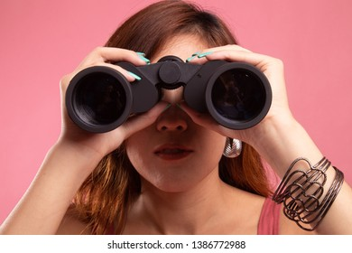 Young Asian woman with binoculars on pink background