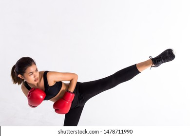 Young Asian woman in black sportswear and red leather boxing gloves practicing kickboxing with raised leg on white background. Female boxer doing high kick