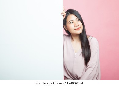 Young Asian woman with blank sign on pink background