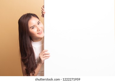 Young Asian woman with blank sign   on beige background.