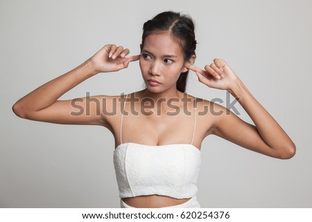 Young Asian woman block both ears with finger  on gray background