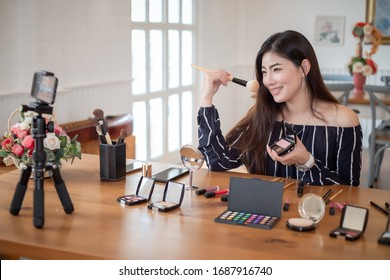Young asian woman blogger with makeup cosmetics recording video clip online by smartphone at home. Teaching and selling product online concept.