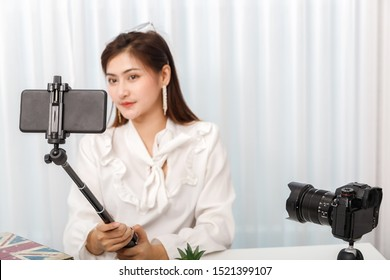 Young asian woman blogger selfie herself with smart phone while recording vlog video live streaming. blogger and vlogger online influencer on social media concept.