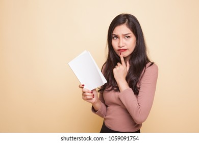 Young Asian woman with a book is thinking on beige background