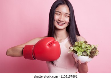 Young Asian woman with boxing glove and salad on pink background