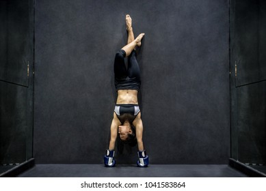Young Asian woman with boxing gloves doing exercise, handstand posing in fitness gym. healthy lifestyle concept