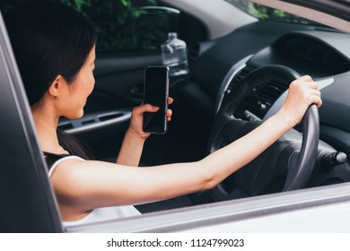 Young Asian woman calling and using a smart phone while driving a car. Dangerous and risky driving concept