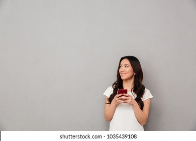 Young asian woman in casual t-shirt chatting or browsing internet on mobile phone and looking aside on copyspace isolated over gray background