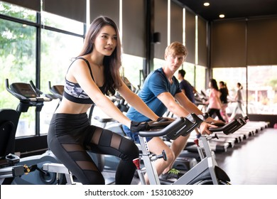 Young Asian woman and Caucasian man on machine fitness training at gym