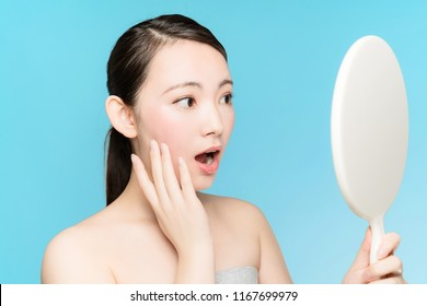Young asian woman checking her face with hand mirror.