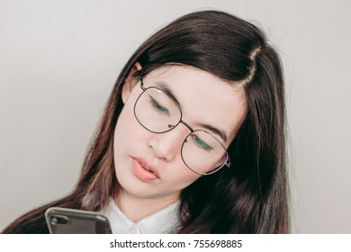 Young asian woman checking on her smartphone