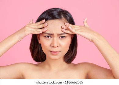 young Asian woman checking wrinkles on her forehead on pink background. women health care beauty medical concept