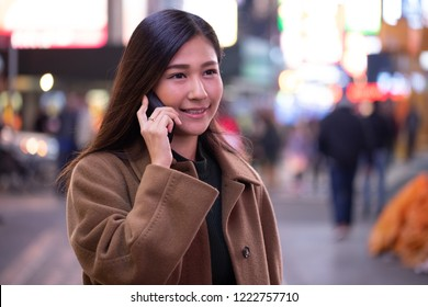 Young Asian woman in city at night talking on cell phone