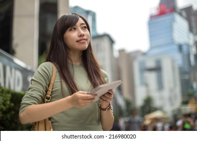 Young Asian woman in city using tablet pc on a street