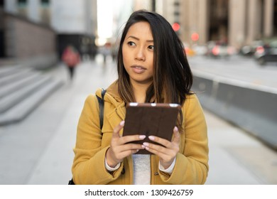 Young Asian woman in city walking street using tablet computer