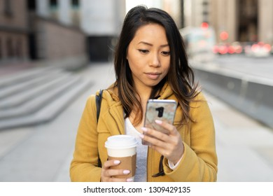Young Asian woman in city walking texting cell phone