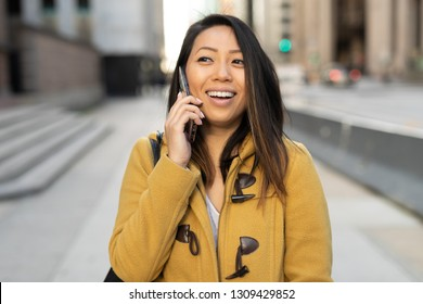 Young Asian woman in city walking talking on cell phone