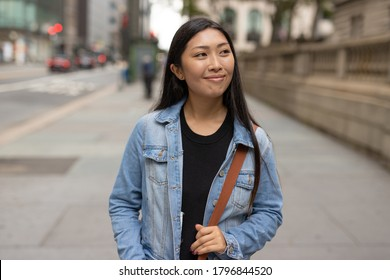 Young Asian woman in city walking street smiling happy face