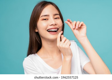 Young Asian woman cleaning braces on teeth with dental floss on blue background, Concept oral hygiene and health care.